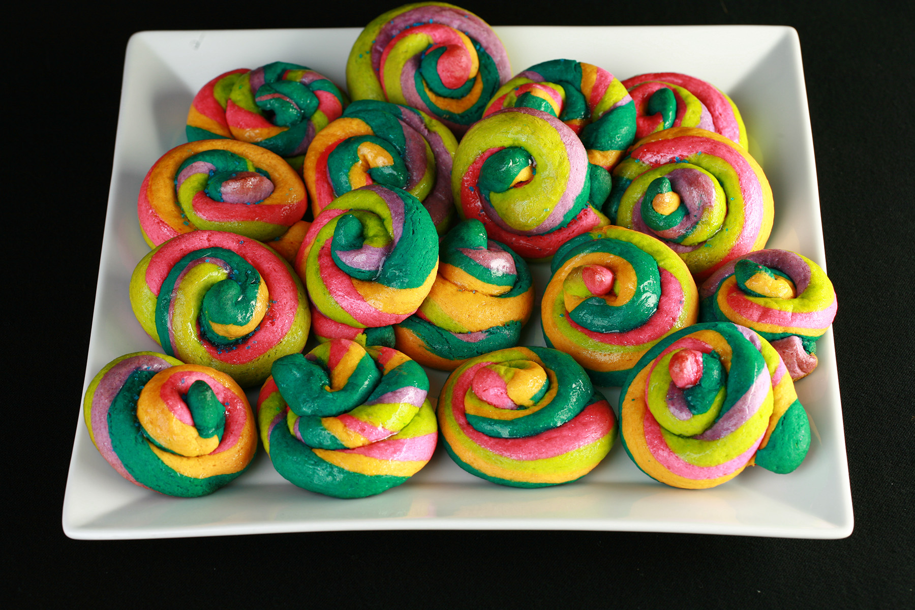 """A white, square plate piled with gluten-free unicorn poop cookies.  They are brightly coloured cookie """"poops"""" made from brightly coloured twists of cookie dough."""