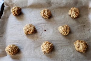 Balls of gluten-free oatmeal cookie dough, arranged on a parchment lined baking sheet.