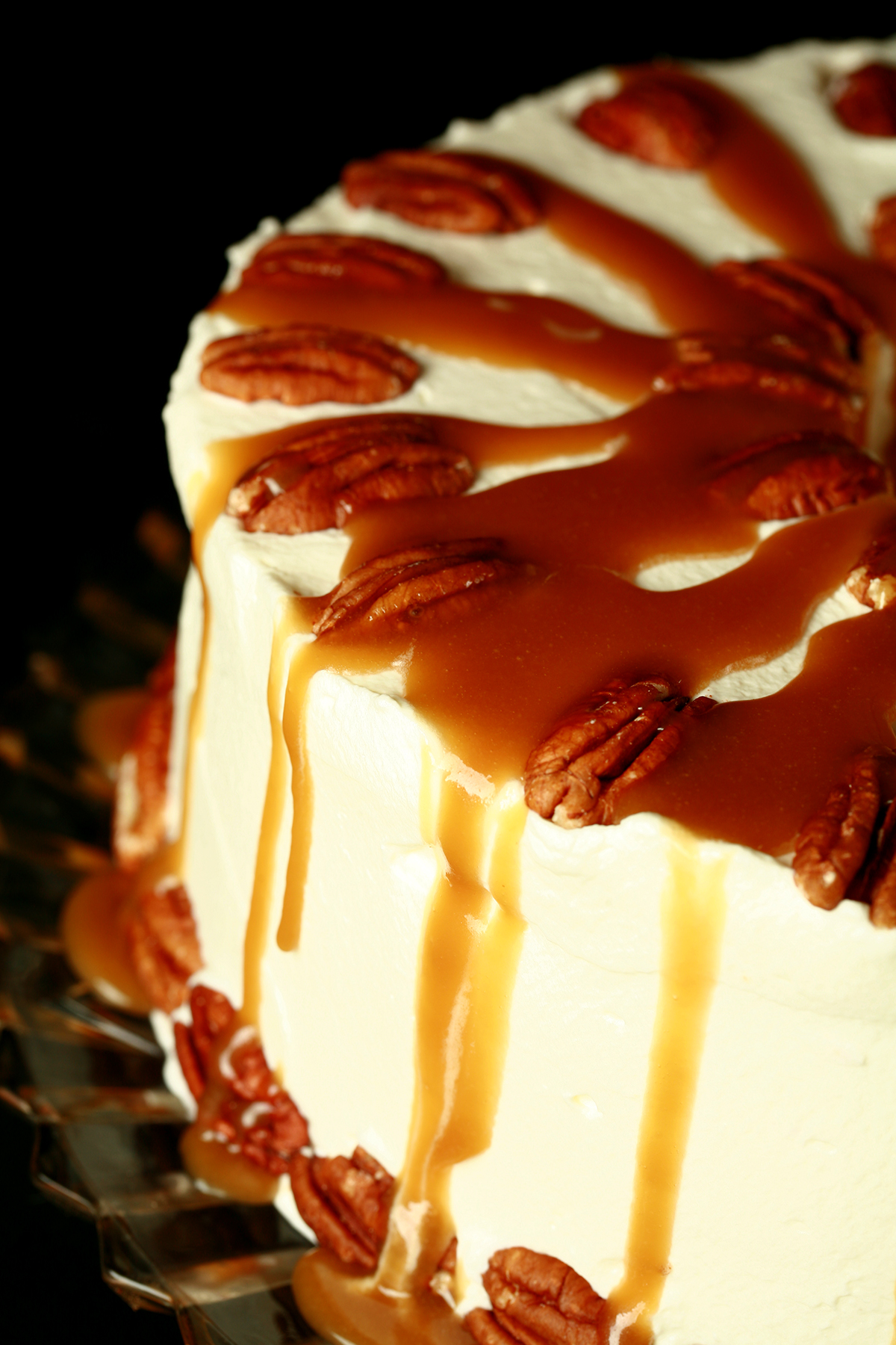 A close up view of a schmoo torte - layers of pecan angel food cake and whipped cream, topped with pecans and with caramel sauce drizzled all over it!