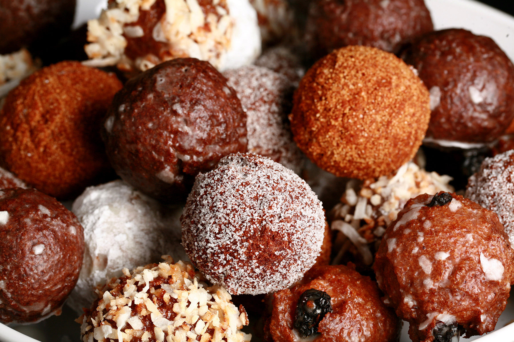 A close up view of an assortment of gluten-free timbits: Toasted coconut, chocolate glazed, cinnamon sugar, powdered sugar, and dutchie versions are all visible.