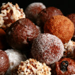 A close up view of an assortment of gluten-free doughnut holes: Toasted coconut, chocolate glazed, cinnamon sugar, powdered sugar, and dutchie versions are all visible.