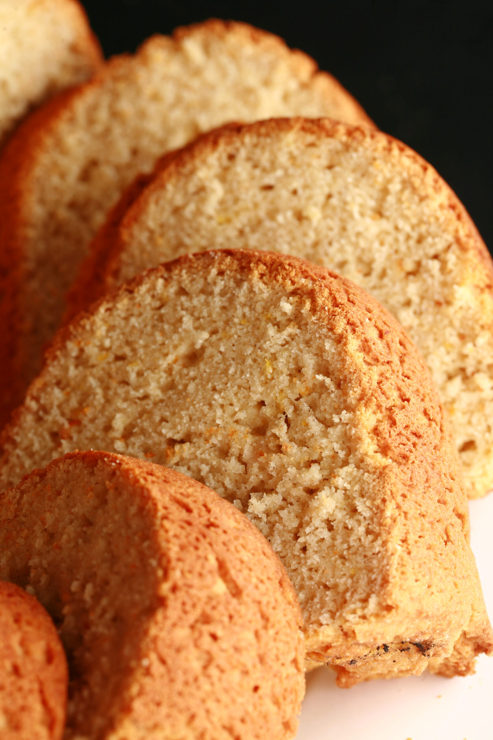 Sliced of a pale yellow bundt shaped loaf of bread.