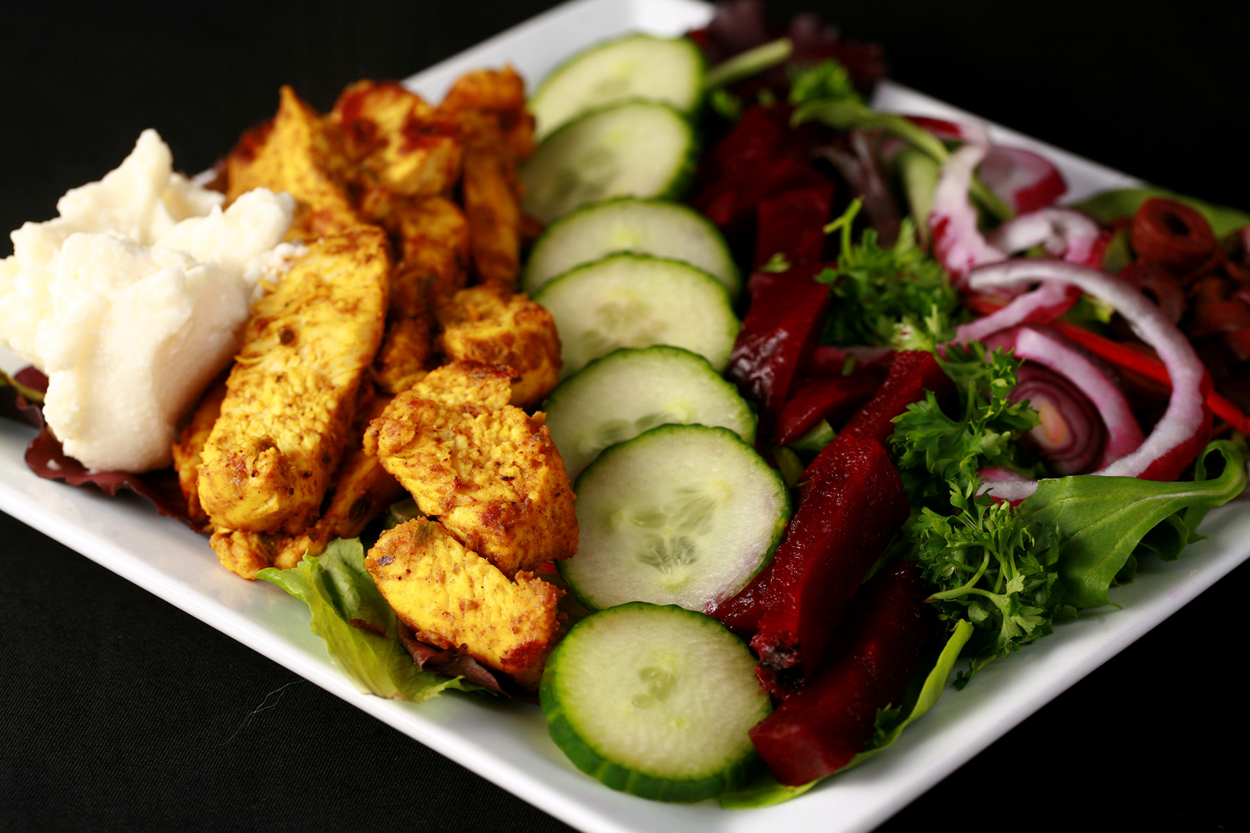 An AIP chicken shawarma salad, with stripes of chicken, pickled beets, cucumbers, red onions, and toum.