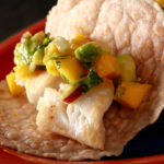 Cassava flour paleo fish tacos, with mango salsa, on a red plate.