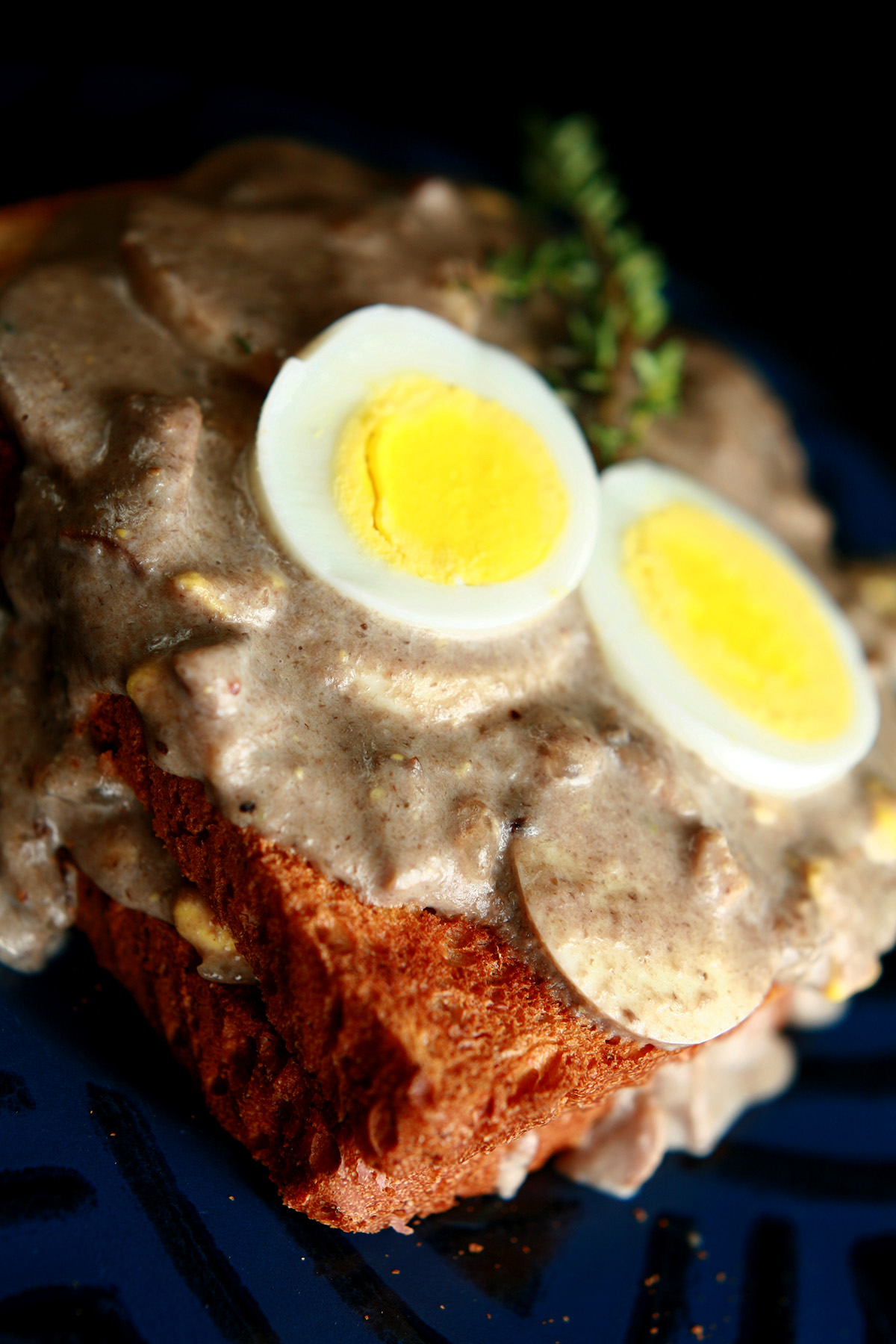 Gluten-Free Mushroom Soup and Eggs on Toast, garnished with hardboiled egg slices and thyme.