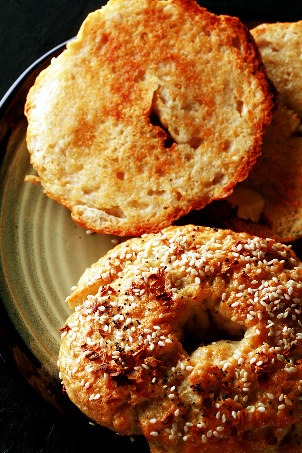 A close up view of two toasted gluten-free bagels on a plate. One is coated with everything seasoning.