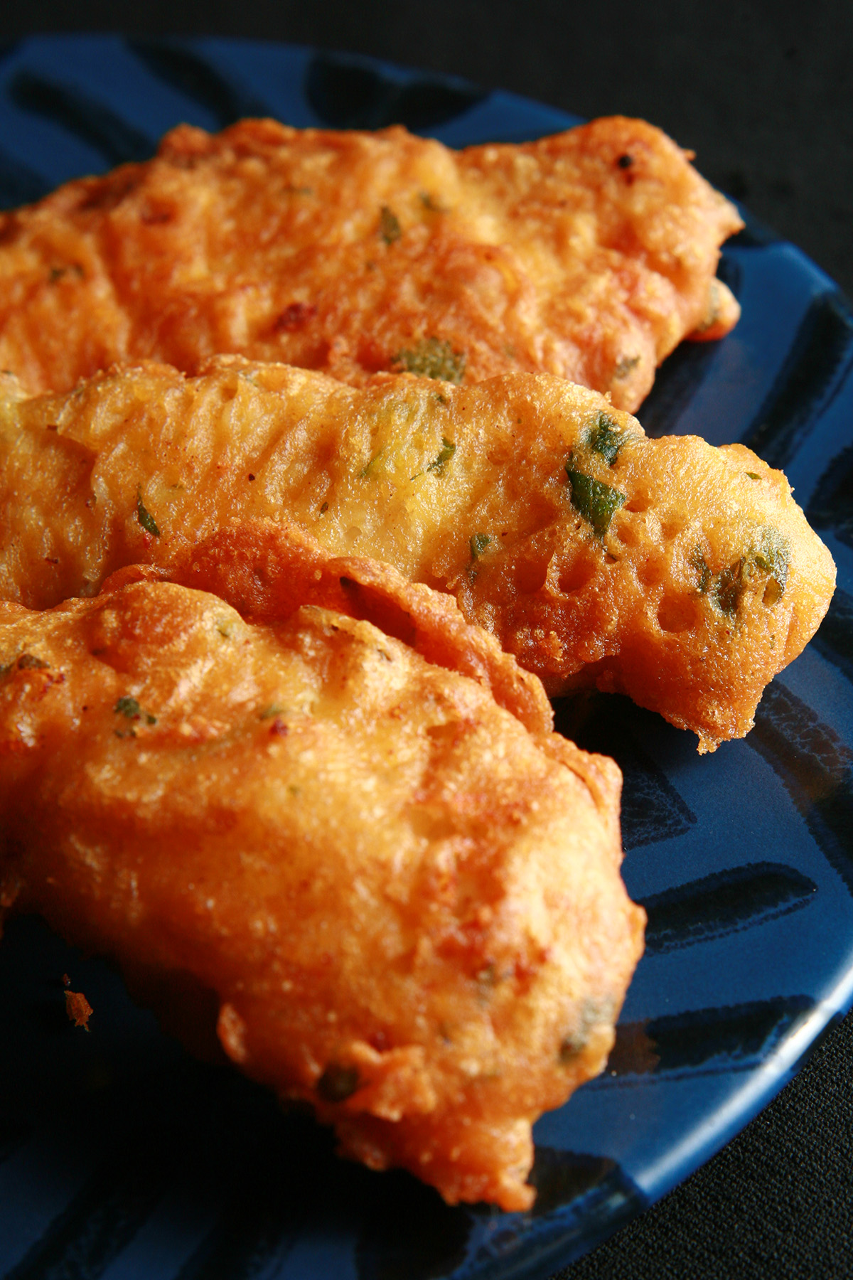 Several strips of gluten-free chicken pakora on a blue plate. They are golden deep fried, with flecks of green cilantro.
