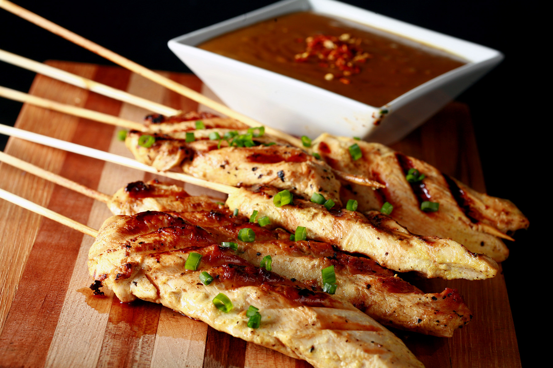 Several skewers of gluten-free chicken satay on a striped cutting board.  They are sprinkled with green onions and sitting next to a bowl of peanut sauce.