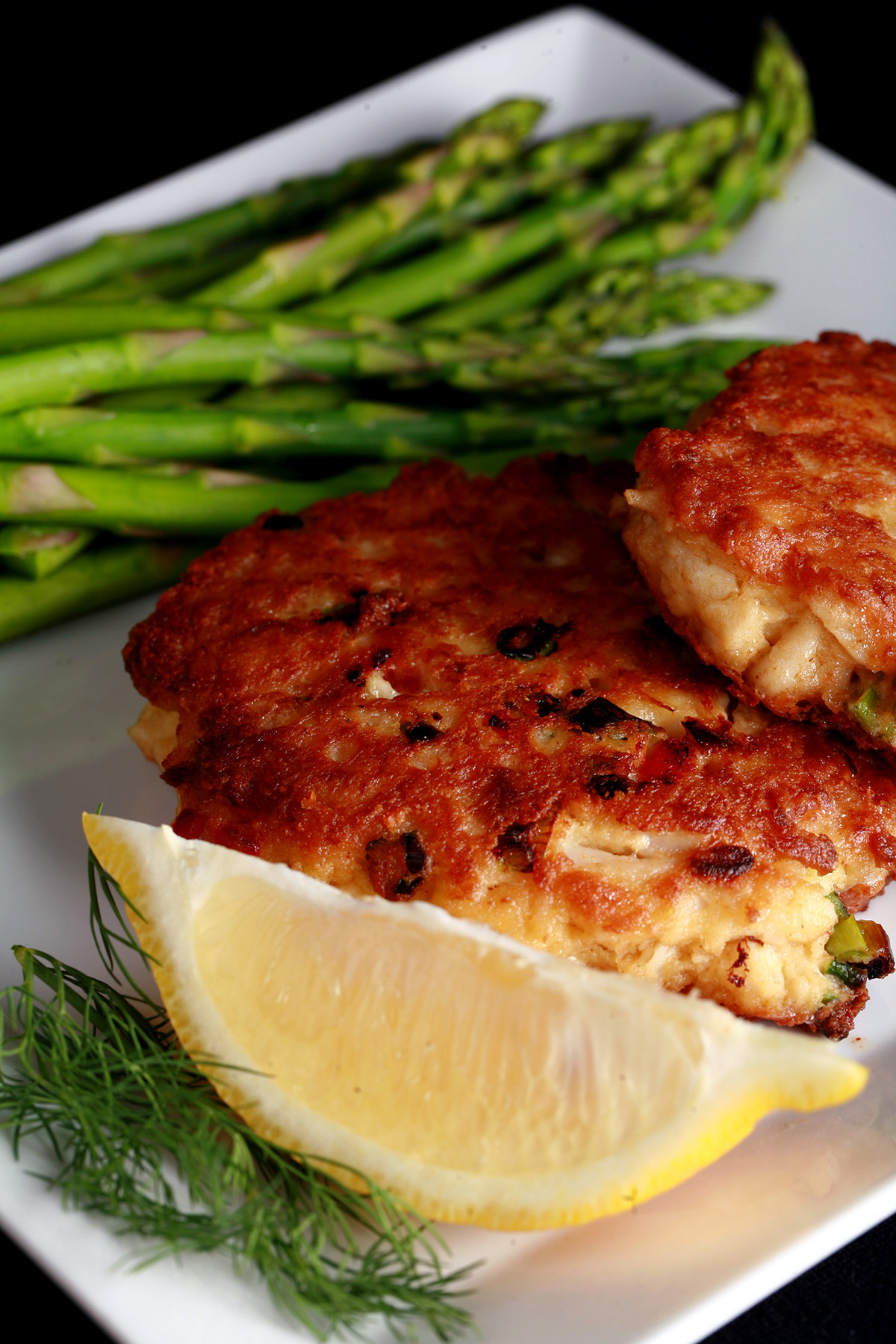 2 Gluten-free Crab Cakes on a plate with asparagus, a lemon slice, and some fresh dill.