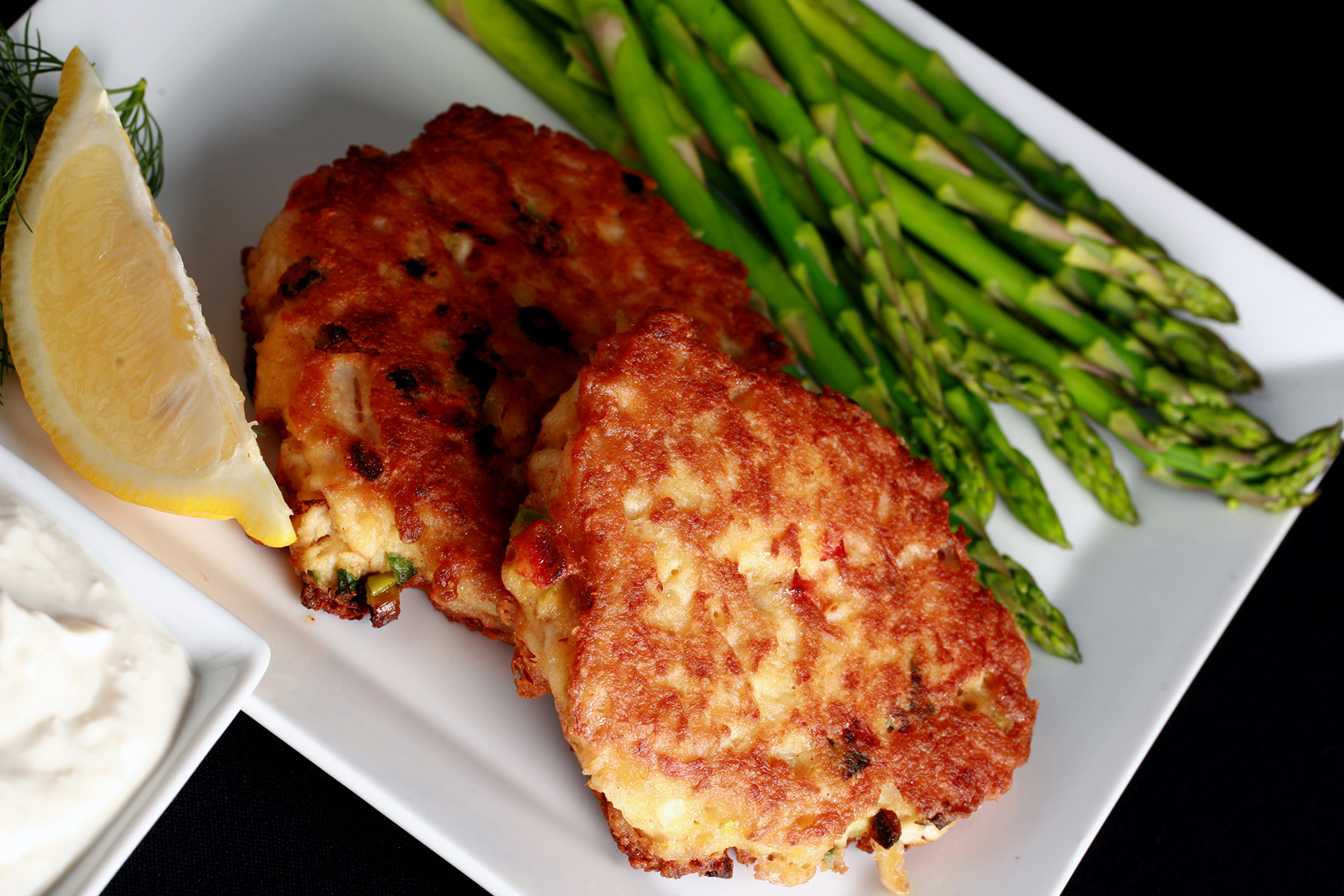 2 Gluten-free Crab Cakes on a plate with asparagus, a lemon slice, and some fresh dill.  There is a small bowl of horseradish sauce next to it.