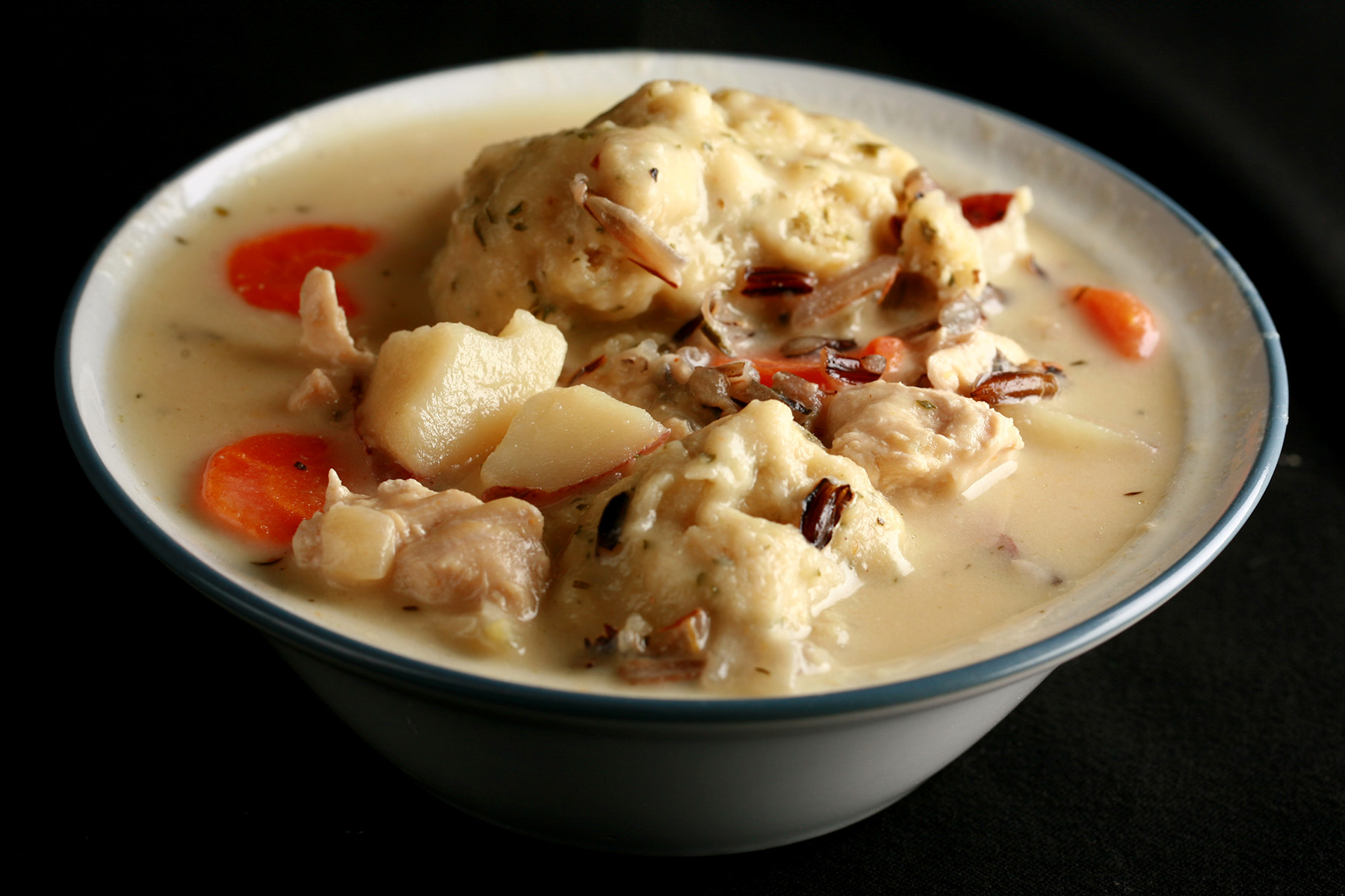 A bowl of gluten-free creamy chicken wild rice soup with dumplings.