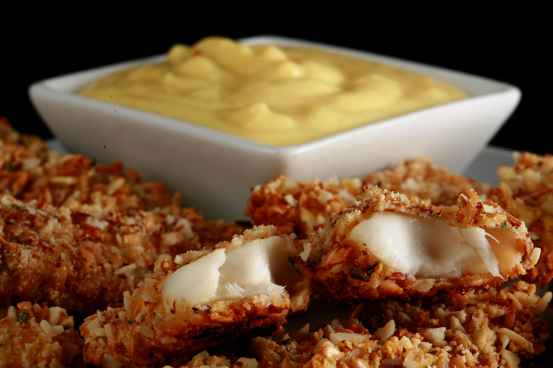 A plate of gluten-free fish fingers with a small bowl of savoury custard on the plate.