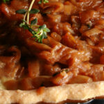 A close up view of a gluten-free French onion soup tart. The top is covered in caramelized onions and garnished with thyme.