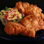 3 pieces of gluten-free fried chicken on a plate, next to a small bowl of colourful coleslaw.