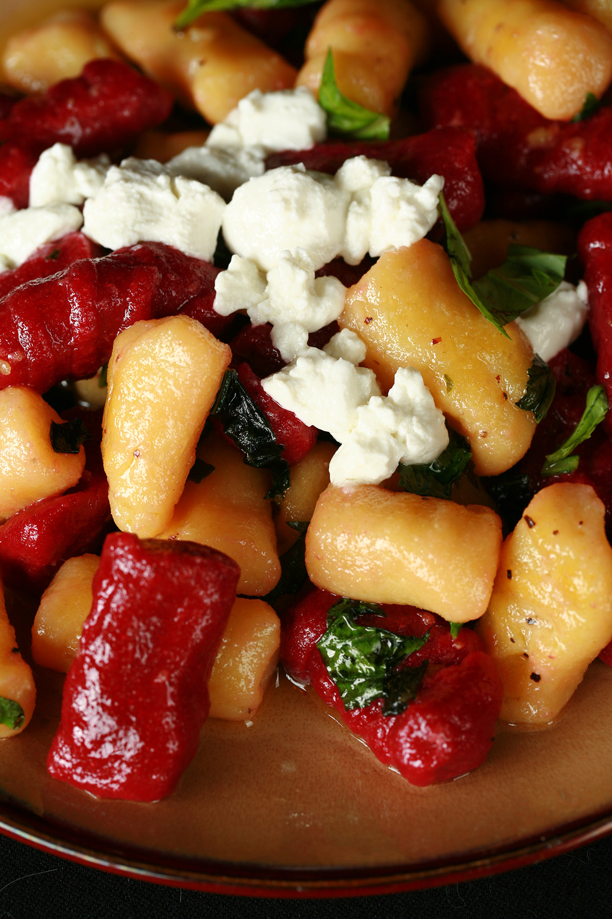 A plate of red and yellow roasted beet gnocchi. It's topped with crumbled goat cheese and fresh basil.