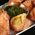 Several Gluten-Free Samosa on a tray, surrounding a small bowl of cilantro chutney.