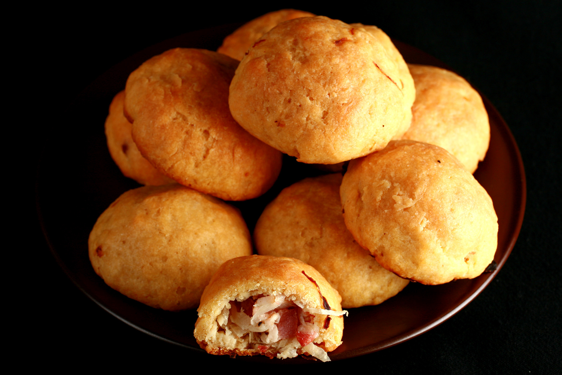 A pile of gluten-free sauerkraut balls on a small plate. One is broken in half, showing the bacon and onion mixture inside.