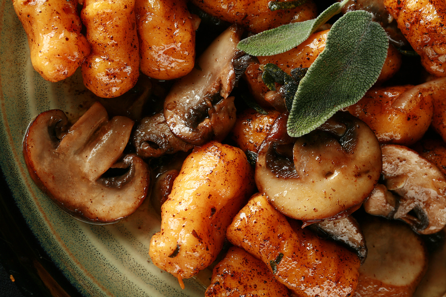 Close up view of AIP sweet potato gnocchi with mushrooms and sage.