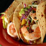 A red plate with shrimp tacos. The tacos are made from gluten-free hybrid tortillas, and look like a more yellow version of flour tortillas.