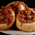Several Gluten-Free Pecan Pie cookies on a white plate. They are golden brown, with a pecan and brown sugar topping.