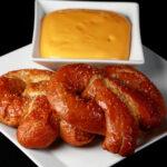 2 gluten-free soft pretzels on a plate, beside a bowl of mustard-cheddar dip.