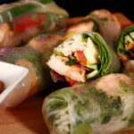 Several mango-shrimp spring rolls on a cutting board, along with a small bowl of peanut sauce.